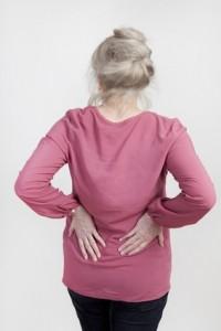 eine aeltere Frau hält sich den Rücken vor schmerzen
